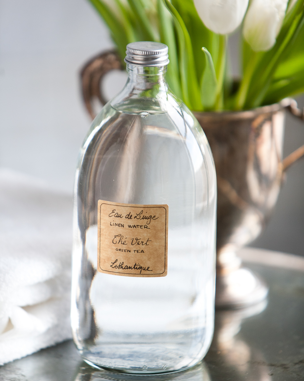 Linen water in a clear bottle with a hand written label and white tulips.