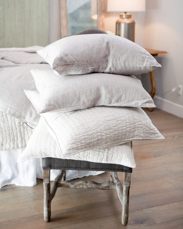 Linen pillows stacked on a chair with a bed in the background