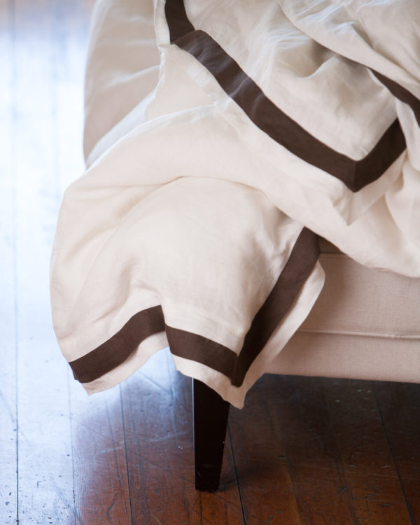 Linen duvet with a brown stripe around the edge sitting on the corner of a footstool.