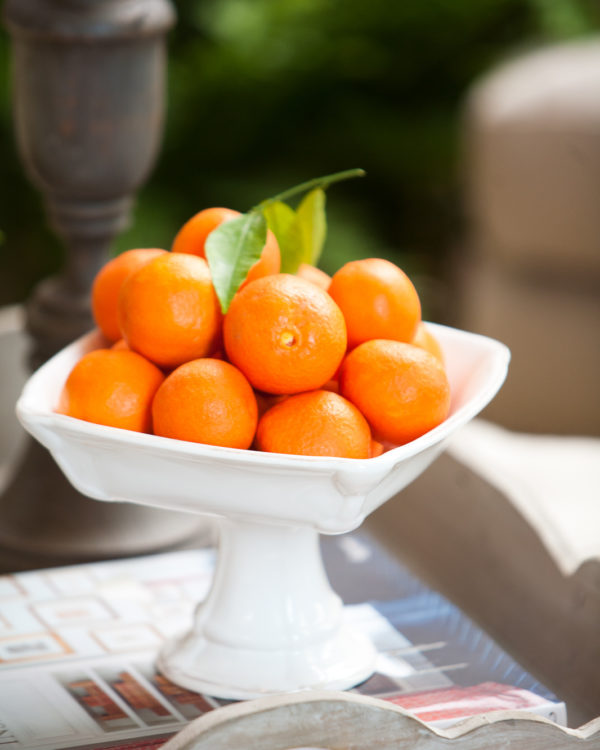 Tangerines in a white dish with a pedestal.