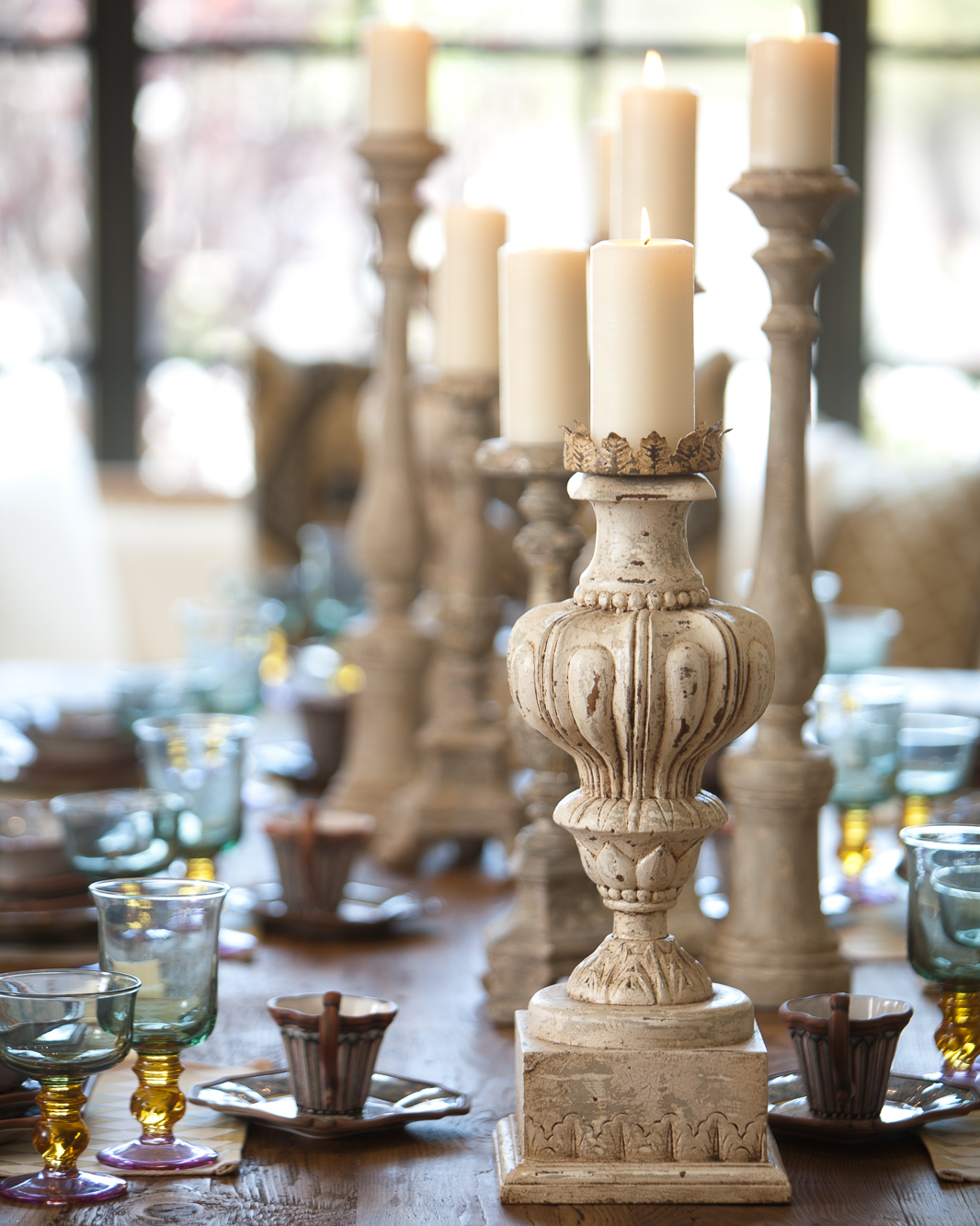 Tall candlesticks and lit candles in the center of an elegantly set table.
