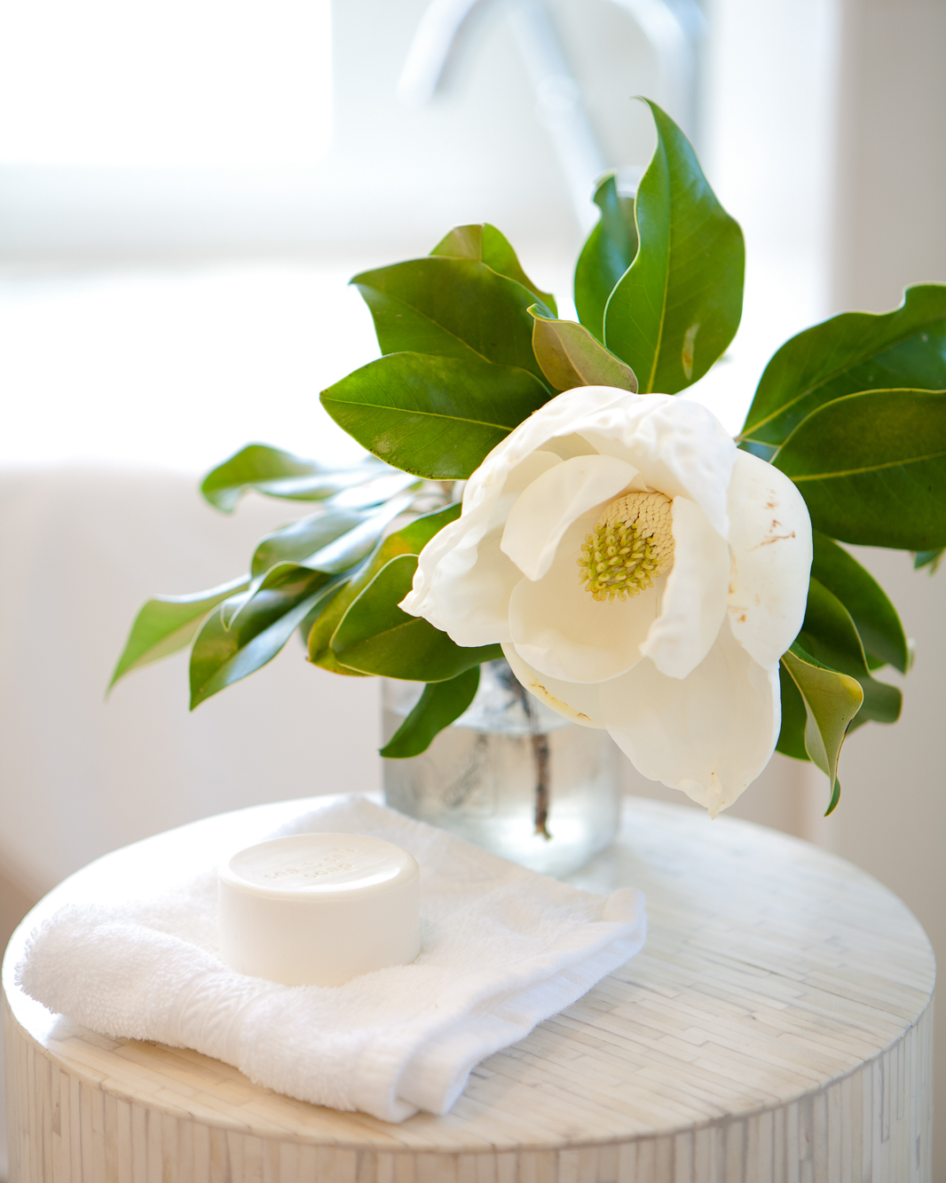 Magnolia blossom in a clear vase on a small table next