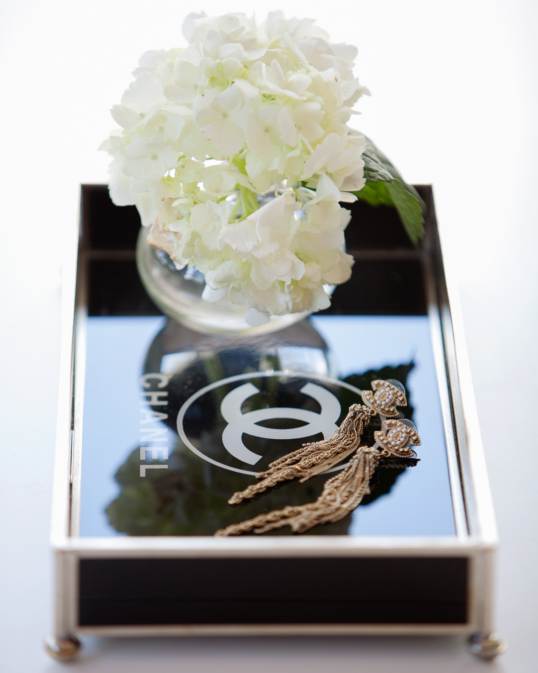Chanel jewelry tray with gold, drapey earrings and white hydrangeas.