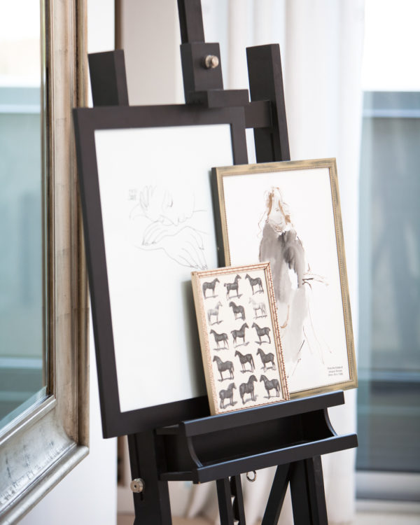 Three black an white, framed prints of illustrations on a large art easel next to a mirror.