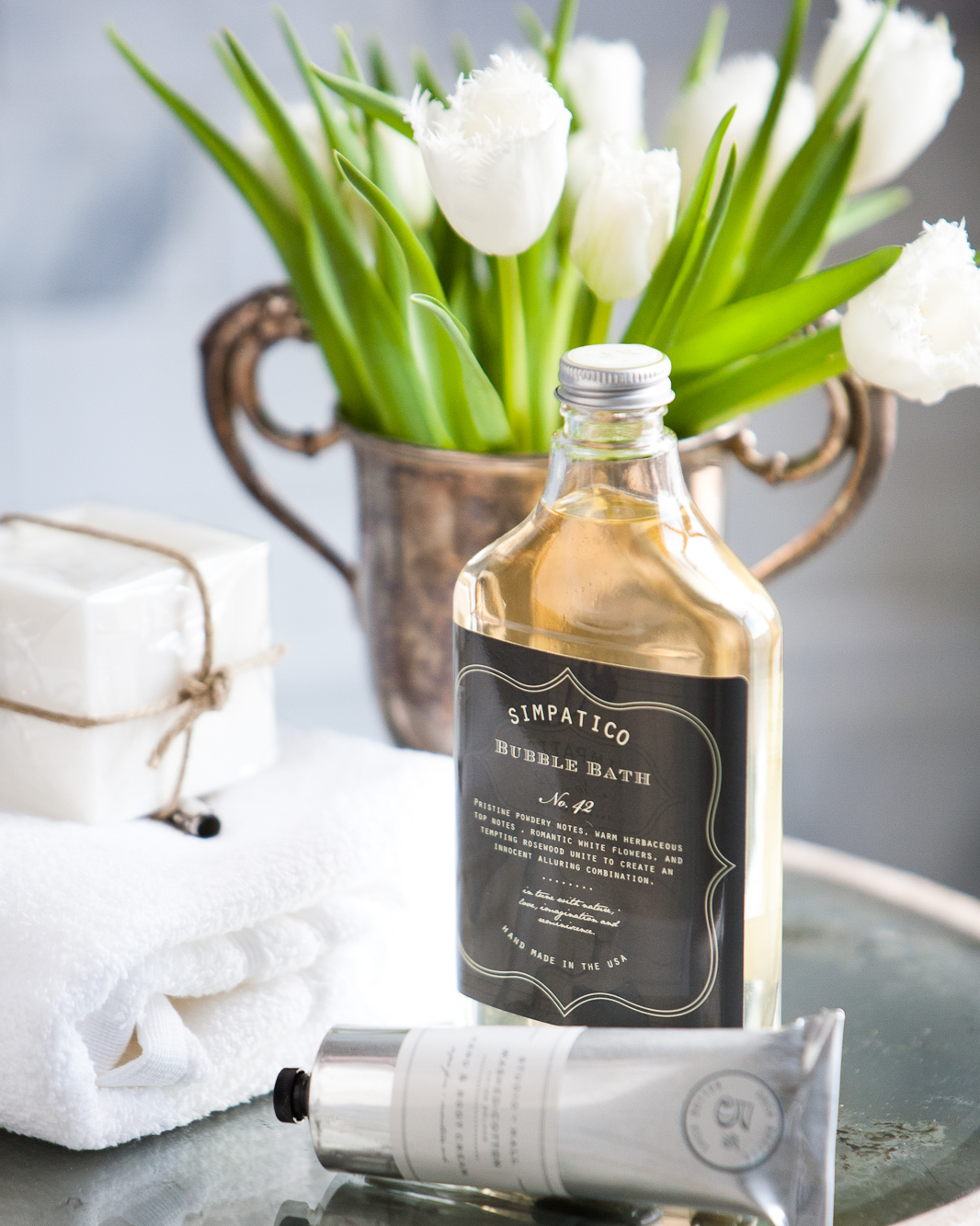 Bottle of Simpatico brand bubble bath on a tray with soap and a towel and tulips in the background.