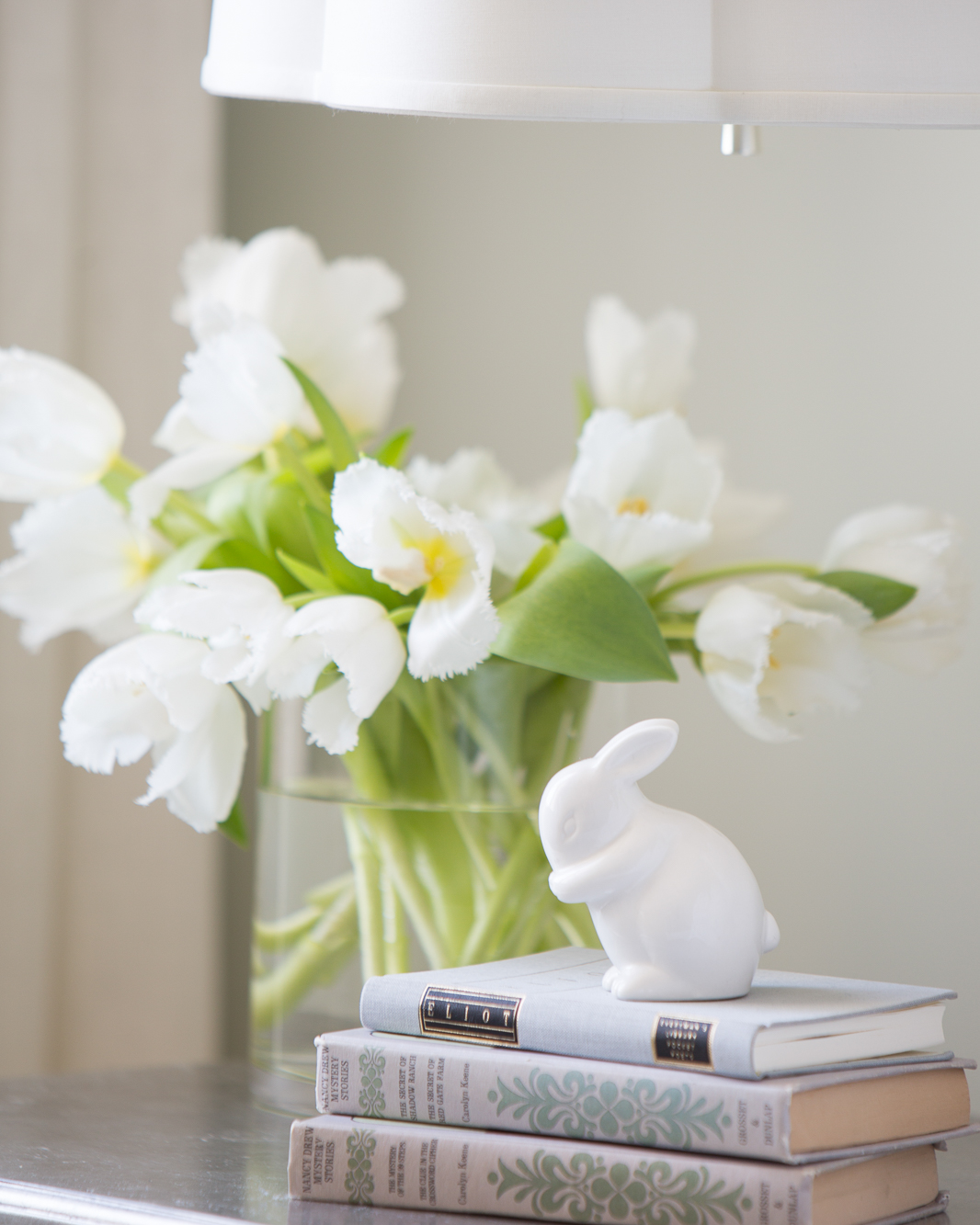White bunny statue sitting on books, on a side table next to white tulips.