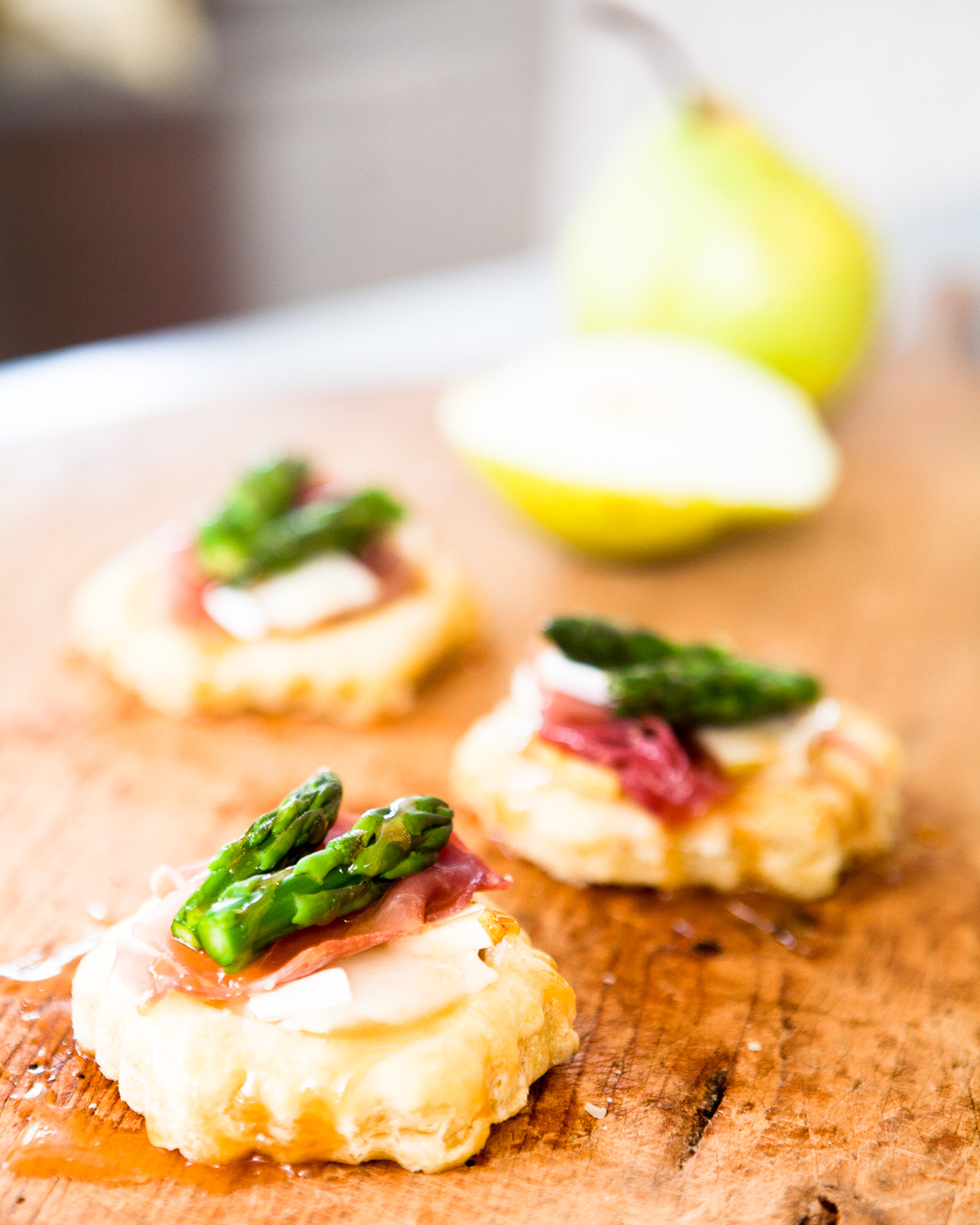 Pear, prosciutto, brie cheese and asparagus puff pastry tarts.