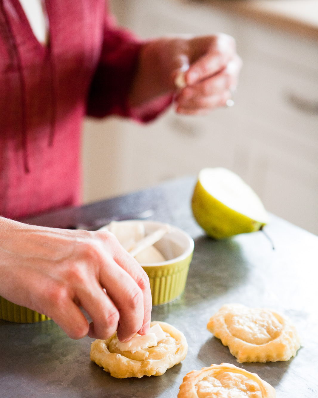 Hands making puff pastry pear and brie cheese tarts.
