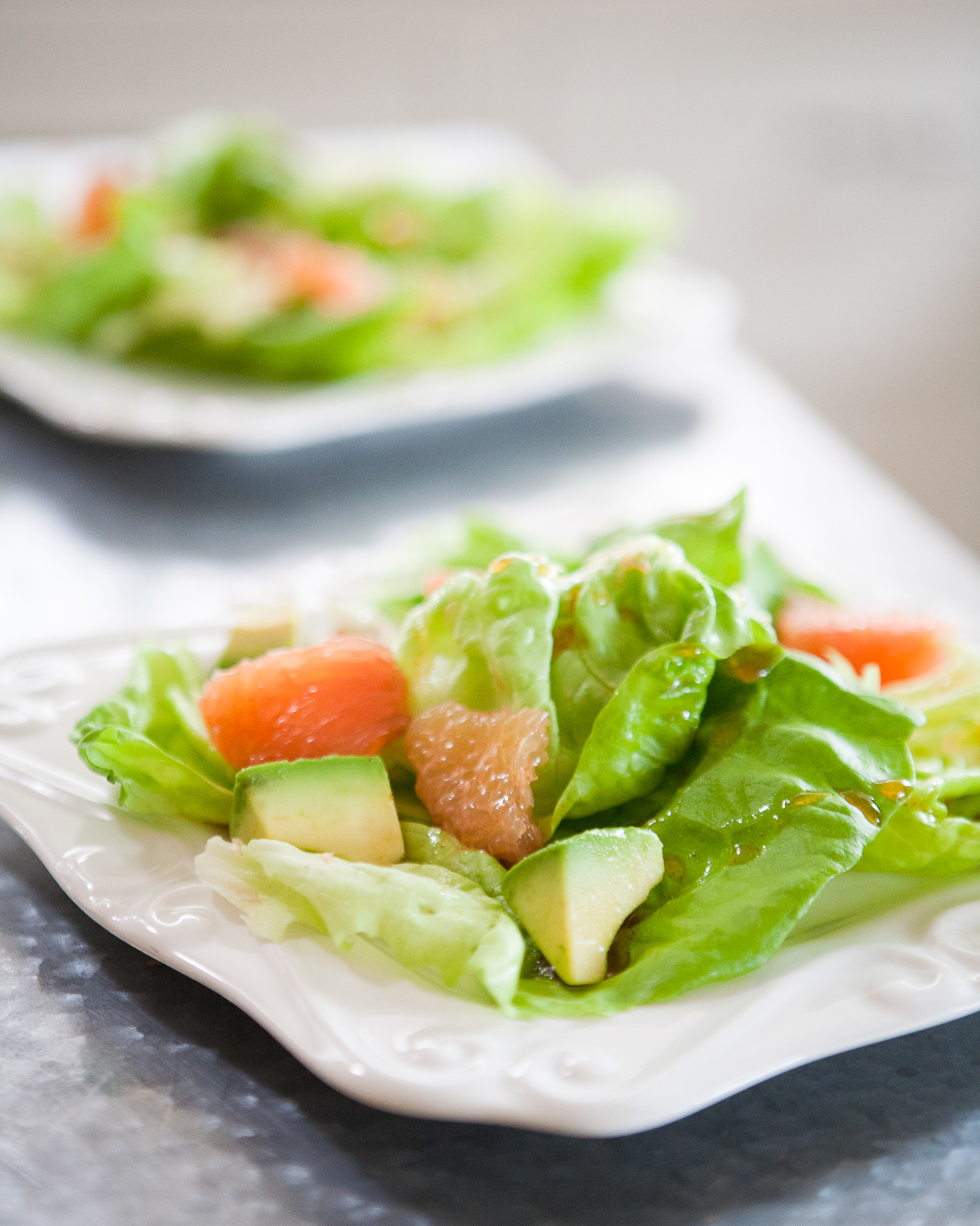 Butter Leaf salad with avocado and grapefruit on a white plate.