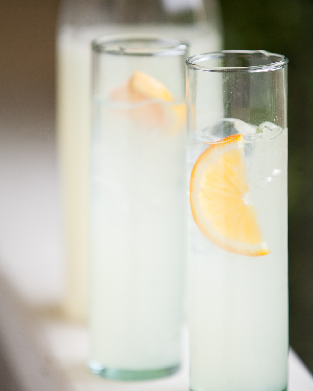 Two glasses of lemonade with orange slices in front of a carafe.