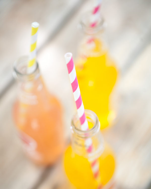 Paper straws coming out of three citrus sodas.