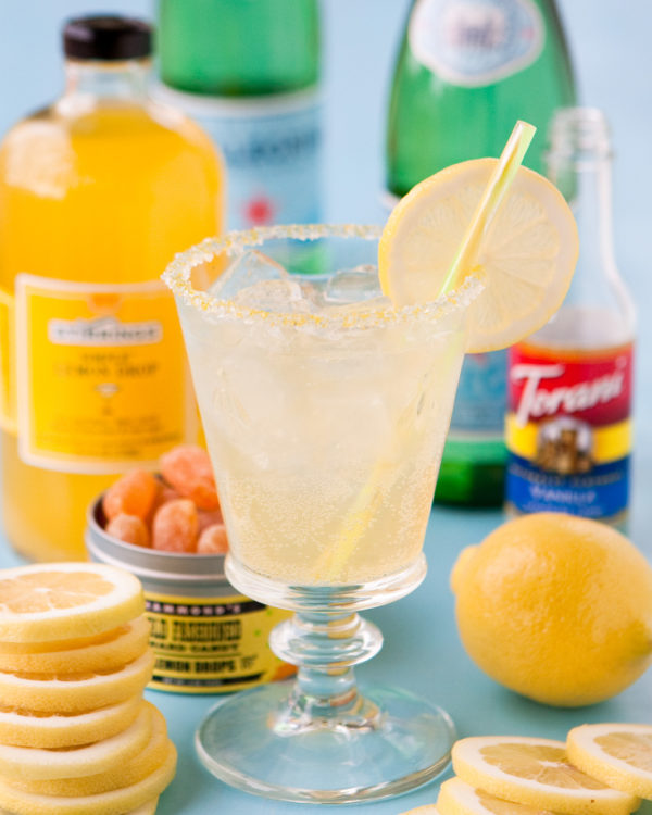 A lemon cocktail with lemon slices and sugar on the rim.