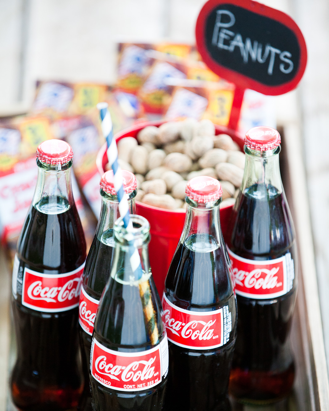 A tray of old fashioned coca-cola bottles, peanuts and crackerjack. Take me out to the ball game.