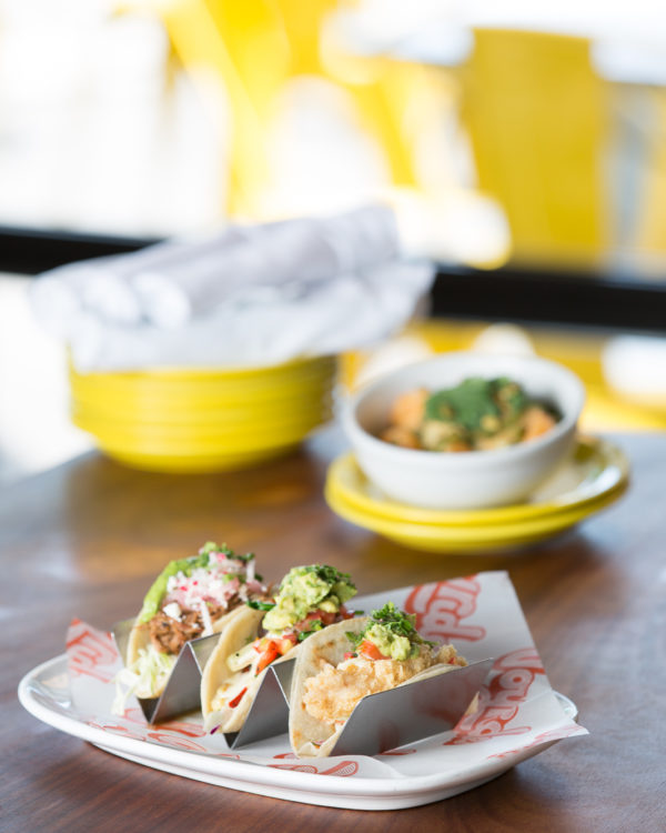 Three fancy tacos from Joyride Tacos in Gilbert, Arizona on a wooden table.
