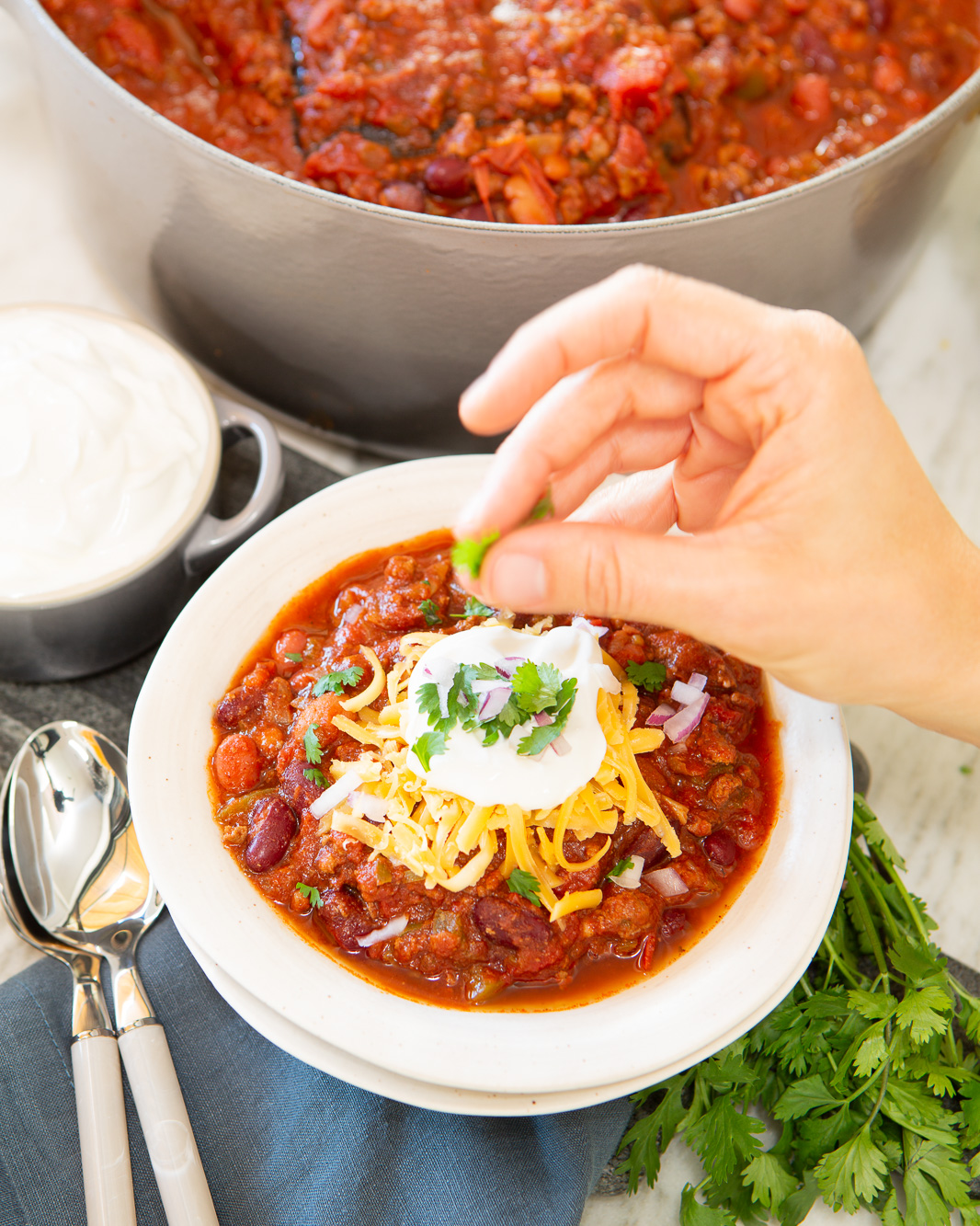 A hot bowl of chile and beans with cheese, red onions, cilantro and sour cream. A woman's hand is placing the final garnish in preparation of serving. A big pot of chile is in the background.